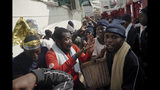 Migrants celebrate after receiving news of their assigned place of safety, aboard the Ocean Viking in the Mediterranean Sea, Monday, Sept. 23, 2019. Italy has granted the humanitarian ship permission to sail to the port of Messina in Italy to disembark 182 people rescued north of Libya. (AP Photo/Renata Brito)