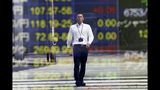 A man is reflected on the electronic board of a securities firm in Tokyo, Tuesday, Sept 24, 2019. Shares have edged higher in Asia as U.S. Treasury Secretary Steven Mnuchin confirmed that China-U.S. trade talks were due to resume in two weeks' time. The Shanghai Composite index rose 0.8% and shares also rose in Tokyo and Hong Kong. (AP Photo/Koji Sasahara)
