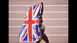 Gold medallist Dina Asher-Smith, of Great Britain, celebrates with the Union flag after winning the women's 200 meter final at the World Athletics Championships in Doha, Qatar, Wednesday, Oct. 2, 2019. (AP Photo/Martin Meissner)