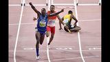 Gold medallist Grant Holloway, of the United States, celebrates as he crosses the finish line ahead of Orlando Ortega, of Spain,, center in red, to win the men's 110 meter hurdles final at the World Athletics Championships in Doha, Qatar, Wednesday, Oct. 2, 2019. (AP Photo/Martin Meissner)