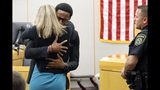 Botham Jean's younger brother Brandt Jean hugs convicted murderer and former Dallas Police Officer Amber Guyger after delivering his impact statement to her after she was sentenced to 10 years in jail, Wednesday, Oct. 2, 2019, in Dallas. Guyger shot and killed Botham Jean, an unarmed 26-year-old neighbor in his own apartment last year. She told police she thought his apartment was her own and that he was an intruder. (Tom Fox/The Dallas Morning News via AP, Pool)