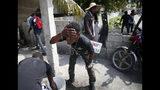 Un manifestante se lava la cara para tratar de aliviar las molestias por el gas lacrimógeno lanzado por la policía durante una protesta exigiendo la renuncia del presidente Jovenel Moise, en Puerto Príncipe, Haití, el viernes 4 de octubre de 2019. (Foto AP/Rebecca Blackwell)