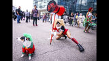 An attendee dressed as Harley Quinn poses with her Joker dog during New York Comic Con at the Jacob K. Javits Convention Center on Friday, Oct. 4, 2019, in New York. (Photo by Charles Sykes/Invision/AP)