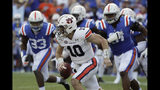 Auburn quarterback Bo Nix (10) scrambles from the pocket as Florida linebacker David Reese II (33) and defensive lineman Marlon Dunlap Jr. (91) pressure during the first half of an NCAA college football game, Saturday, Oct. 5, 2019, in Gainesville, Fla. (AP Photo/John Raoux)