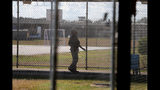 A guard walks on a path between yards during a media tour inside the Winn Correctional Center in Winnfield, La., Thursday, Sept. 26, 2019. Formerly a medium-security prison, Winn has a dining hall, outdoor soccer fields, a gymnasium, and a 200-person chapel built by former inmates. (AP Photo/Gerald Herbert)