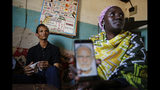 """Gerald Erebon sits with his aunt, Scolastica Apayo, as she holds a phone displaying a photo of the Rev. Mario Lacchin, during an interview at her home in the Isiolo area of the Archers Post settlement in Kenya on Sunday, June 30, 2019. Scolastica said her sister, Sabina Losirkale, finally told her the secret in 2012, two weeks before she died. """"Now that my days are over,"""" her sister told her, she could reveal all: """"When Gerald will ask you who's his father, just tell him: Father Mario."""" (AP Photo/Brian Inganga)"""