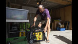 Joe Wilson pulls his generator out in the garage of his home, which is in an area that is expected to lose power early Wednesday, in the East Foothills area of San Jose, Calif., Tuesday, Oct. 8, 2019. Millions of people were poised to lose electricity throughout northern and central California after Pacific Gas & Electric Co. announced Tuesday it would shut off power in the largest preventive outage in state history to try to avert wildfires caused by faulty lines. (Randy Vazquez/San Jose Mercury News via AP)