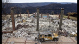 FILE - In this Dec. 3, 2018, file photo, a vehicle rests in front of a home leveled by the Camp Fire in Paradise, Calif. Two years to the day after some of the deadliest wildfires tore through Northern California wine country, two of the state's largest utilities were poised Tuesday, Oct. 8, 2019, to shut off power to more than 700,000 customers in 37 counties, in what would be the largest preventive shut-off to date as utilities try to head off wildfires caused by faulty power lines. (AP Photo/Noah Berger, File)