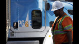 FILE - In this Aug. 15, 2019, file photo, a Pacific Gas & Electric worker walks in front of a truck in San Francisco. Two years to the day after some of the deadliest wildfires tore through Northern California wine country, two of the state's largest utilities were poised Tuesday, Oct. 8, 2019, to shut off power to more than 700,000 customers in 37 counties, in what would be the largest preventive shut-off to date as utilities try to head off wildfires caused by faulty power lines. (AP Photo/Jeff Chiu, File)