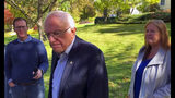 """In this image taken from video, Democratic presidential candidate Sen. Bernie Sanders, I-Vt., speaks we reporters outside his home, Tuesday, Oct. 8, 2019, in Burlington, Vt. His wife, Jane O'Meara Sanders listens at right. Sanders says he was """"dumb"""" not to have listened to the symptoms he was experiencing before he was stricken with a heart attack last week. (AP Photo/Wilson Ring)"""