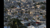 People pass the time on rooftops as afternoon turns to evening in Port-au-Prince, Haiti, Tuesday, Oct. 8, 2019. Haiti has entered its fourth week of anti-government protests that have paralyzed the economy and shuttered schools as demonstrators demand the resignation of President Jovenel Moise. (AP Photo/Rebecca Blackwell)