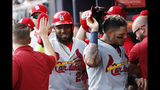 St. Louis Cardinals' Marcell Ozuna, left, and Yadier Molina, are greeted by teammates after scoring off Tommy Edman's doubles during the first inning of Game 5 of their National League Division Series baseball game against the Atlanta Braves, Wednesday, Oct. 9, 2019, in Atlanta. (AP Photo/John Bazemore)