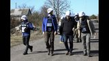 Deputy Head of the OSCE Special Monitoring Mission, Mark Etherington, second right, and other members of OSCE walk through a street near a frontline in Petrovske, Ukraine, Wednesday, Oct. 9, 2019. At least one Ukrainian police officer has been injured in scuffles between police and activists who have arrived to the frontline in eastern Ukraine to derail the pullback of government forces. (AP Photo/Alexei Alexandrov)