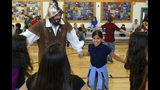 FILE - In this Wednesday, Aug. 30, 2017 file photo, Edwin Quintana, left, dressed as a 17th Century Spanish conquistador, dances with fifth grader Kaylee Pacheco and other students at Tesuque Elementary school in Tesuque, N.M. In recent years, the conquistador and all the effigies connected to it have come under intense criticism from Native American activists who say the image glorifies indigenous genocide and needs to be removed from schools, streets and seals. (AP Photo/Morgan Lee,File)