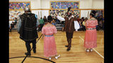 In this Aug. 30, 2017, file photo, Edwin Quintana, second from right, dressed as a 17th Century Spanish, conquistador motions to a crowd of students at Tesuque Elementary school in Tesuque, N.M., during an annual presentation of Spanish colonial culture and history that honors conquistador Don Diego de Vargas. In recent years, the conquistador and all the effigies connected to it have come under intense criticism from Native American activists who say the image glorifies indigenous genocide and needs to be removed from schools, streets and seals. (AP Photo/Morgan Lee)