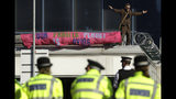 Police Officers stand guard as an Extinction Rebellion demonstrator gestures with a banner on a raised area at City Airport in London, Thursday, Oct. 10, 2019. Some hundreds of climate change activists are in London during a fourth day of world protests by the Extinction Rebellion movement to demand more urgent actions to counter global warming. (AP Photo/Matt Dunham)