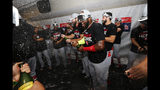 St. Louis Cardinals' Marcell Ozuna, center, celebrates with teammates in the clubhouse after the Cardinals beat the Atlanta Braves 13-1 in Game 5 of their National League Division Series baseball game Wednesday, Oct. 9, 2019, in Atlanta. (AP Photo/John Bazemore)