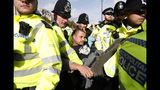 A climate change protester is arrested and carried off by police in Trafalgar Square in London, Thursday, Oct. 10, 2019. Some hundreds of climate change activists are in London during a fourth day of world protests by the Extinction Rebellion movement to demand more urgent actions to counter global warming. (AP Photo/Alastair Grant)