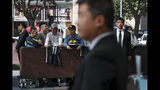 Chinese security officers stand guard as fans carrying jerseys and shoes wait for NBA players to autograph outside the Ritz-Carlton hotel in Shanghai, China, Thursday, Oct. 10, 2019. NBA Commissioner Adam Silver told the Brooklyn Nets and Los Angeles Lakers on Wednesday that the league is still expecting them to play as scheduled this week, even while the rift between the league and Chinese officials continued in ways that clearly suggested the two planned games in Shanghai and Shenzhen were anything but guaranteed. (AP Photo/Andy Wong)