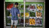 In this Aug. 21, 2019, photo a worker stocks a produce stand at a metro station in Atlanta. On Thursday, Oct. 10, the Labor Department reports on U.S. consumer prices for September. (AP Photo/David Goldman)