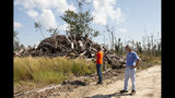 In this Oct. 5, 2019 photo, Daniel Leonard and his father Joe, right, stand near a heap of lumber on their family's property. The massive storm killed more than two dozen people in northern Florida, destroyed hundreds of homes and brought catastrophic damage to the region's timber industry. (AP Photo/Bobby Caina Calvan)