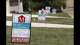 In this Sept. 25, 2019, photo a realty company's signs rest on several lawns in front of newly constructed houses in Brandon, Miss. On Thursday, Oct. 10, Freddie Mac reports on this week's average U.S. mortgage rates. (AP Photo/Rogelio V. Solis)