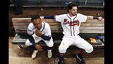Atlanta Braves' Dansby Swanson, right, and Ozzie Albies sit in the dugout after the Braves lost 13-1 to the St. Louis Cardinals in Game 5 of their National League Division Series baseball game Wednesday, Oct. 9, 2019, in Atlanta. (AP Photo/John Amis)