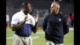 Syracuse coach Dino Babers, left, speaks with North Carolina State coach Dave Doeren before an NCAA college football game in Raleigh, N.C., Thursday, Oct. 10, 2019. (AP Photo/Karl B DeBlaker)