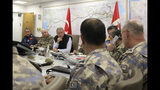 In this photo taken late Wednesday, Oct. 9, 2019, Turkey's Defence Minister Hulusi Akar, center, with Turkish army's top commanders in an operation room at the army headquarters, in Ankara, Turkey. Turkey's Defense Ministry says on Thursday Turkish ground troops are continuing their advance against Kurdish fighters in northern Syria.(Turkish Defence Ministry via AP, Pool)