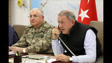 Turkey's Defense Minister Hulusi Akar, right, speaks on the phone alongside Chief of the General Staff of the Turkish Armed Forces Gen. Yasar Guler in an operation room at army headquarters in Ankara, Turkey, Wednesday, Oct. 9, 2019. Turkey's Defense Ministry says Turkish ground forces have moved across the border to fight against Kurdish fighters in northeastern Syria, hours after Turkish jet and artillery pounded areas in Syria's northern border. (Turkish Defence Ministry via AP, Pool)
