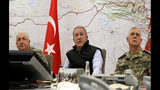 Turkey's Defense Minister Hulusi Akar, center, with Chief of the General Staff of the Turkish Armed Forces Gen. Yasar Guler, left, and Gen. Umit Dundar sit in an operation room at army headquarters in Ankara, Turkey, Wednesday, Oct. 9, 2019. Turkey's Defense Ministry says Turkish ground forces have moved across the border to fight against Kurdish fighters in northeastern Syria, hours after Turkish jet and artillery pounded areas in Syria's northern border. (Turkish Defence Ministry via AP, Pool)