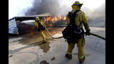 Firefighters try to protect surrounding homes as they battle the Sandalwood Fire in the Villa Calimesa Mobile Home Park in Calimesa, Calif., on Thursday, Oct. 10, 2019. Burning trash dumped along a road sparked a wildfire Thursday that high winds quickly pushed across a field of dry grass and into a Southern California mobile home park, destroying dozens of residences. (Jennifer Cappuccio Maher/The Orange County Register/SCNG via AP)