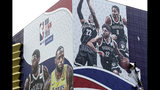 In this Oct. 9, 2019, photo, a worker takes down a billboard advertising an NBA preseason basketball game on Thursday between the Los Angeles Lakers and Brooklyn Nets in Shanghai, China. The NBA has postponed Wednesday's scheduled media sessions in Shanghai for the Brooklyn Nets and Los Angeles Lakers, and it remains unclear if the teams will play in China this week as scheduled. (AP Photo/File)
