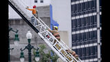 A rescued worker, left, and a firefighter look back at the damaged building after a large portion of a hotel under construction suddenly collapsed in New Orleans on Saturday, Oct. 12, 2019. Several construction workers had to run to safety as the Hard Rock Hotel, which has been under construction for the last several months, came crashing down. It was not immediately clear what caused the collapse or if anyone was injured. (Scott Threlkeld/The Advocate via AP)