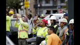 Construction workers look on after a large portion of a hotel under construction suddenly collapsed in New Orleans on Saturday, Oct. 12, 2019. Several construction workers had to run to safety as the Hard Rock Hotel, which has been under construction for the last several months, came crashing down. It was not immediately clear what caused the collapse or if anyone was injured. (Scott Threlkeld/The Advocate via AP)