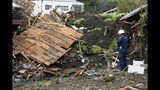 A police officer looks at a house damaged by Typhoon Hagibis, in Tomioka, north of Tokyo, Sunday, Oct. 13, 2019. Rescue efforts for people stranded in flooded areas are in full force after a powerful typhoon dashed heavy rainfall and winds through a widespread area of Japan, including Tokyo.(Kyodo News via AP)