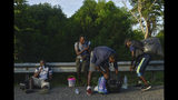 Migrants take a break and check their bags alongside the Highway 200 en route to Huixtla near Tapachula, Chiapas sate, Mexico, Saturday Oct. 12, 2019. Migrants from Africa, Cuba, Haiti, and other Central American countries set off early morning by foot from Tapachula to the southern border of the United States. (AP Photo/Isabel Mateos)