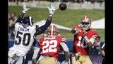 El quarterback de los 49ers de San Francisco, Jimmy Garoppolo (10), lanza un pase al running back Matt Breida (22), mientras el outside linebacker de los Rams de Los Ángeles, Samson Ebukam (50), defiende durante la primera mitad de un juego de la NFL, el domingo 13 de octubre de 2019, en Los Ángeles. (AP Foto/Alex Gallardo)