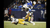 Los Angeles Chargers defensive back Rayshawn Jenkins, right, trips as he runs the ball past Pittsburgh Steelers strong safety Terrell Edmunds, left, and free safety Minkah Fitzpatrick during the first half of an NFL football game, Sunday, Oct. 13, 2019, in Carson, Calif. (AP Photo/Kelvin Kuo)