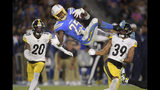 Los Angeles Chargers defensive back Rayshawn Jenkins, center, trips as he runs the ball past Pittsburgh Steelers cornerback Cameron Sutton, left, and lfree safety Minkah Fitzpatrick during the first half of an NFL football game, Sunday, Oct. 13, 2019, in Carson, Calif. (AP Photo/Kyusung Gong)