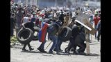 Anti-government demonstrator carry tires to set up a barricade during clashes with police in Quito, Ecuador, Saturday, Oct. 12, 2019. Protests, which began when President Lenin Moreno's decision to cut subsidies led to a sharp increase in fuel prices, have persisted for days. (AP Photo/Fernando Vergara)