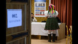 Sporting a folk costume Piroska Kovacsne Bablena takes over her ballot papers at the nationwide local elections in the village of Rimoc, Hungary, Sunday, Oct. 13, 2019. (Peter Komka/MTI via AP)