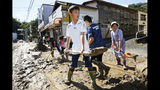 Students and residents scoop dirt as the town is flooded Typhoon Hagibis, in Marumori, Miyagi prefecture, northern Japan, Sunday, Oct. 13, 2019. Rescue efforts for people stranded in flooded areas are in full force after a powerful typhoon dashed heavy rainfall and winds through a widespread area of Japan, including Tokyo.(Kyodo News via AP)