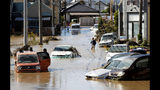 Vehicles are seen in mud water as Typhoon Hagibis hit the city in Sano, Tochigi prefecture, Sunday, Oct. 13, 2019. Rescue efforts for people stranded in flooded areas are in full force after a powerful typhoon dashed heavy rainfall and winds through a widespread area of Japan, including Tokyo.(Kyodo News via AP)