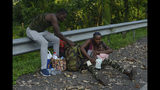 A migrant checks the diaper of a young child alongside the Highway 200 en route to Huixtla near Tapachula, Chiapas state, Mexico, Saturday, Oct. 12, 2019. Migrants from Africa, Cuba, Haiti, and other Central American countries set off early morning by foot from Tapachula to the southern border of the United States. (AP Photo/Isabel Mateos)