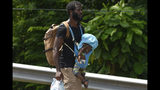A migrant carries a child and water on Highway 200 en route to Huixtla near Tapachula, Chiapas state, Mexico, Saturday, Oct. 12, 2019. Migrants from Africa, Cuba, Haiti, and other Central American countries set off early morning by foot from Tapachula to the southern border of the United States. (AP Photo/Isabel Mateos)