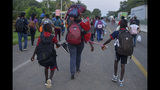 Migrants with bags of belongings walk down the Highway 200 en route to Huixtla near Tapachula, Chiapas, Mexico, Saturday Oct. 12, 2019. Migrants from Africa, Cuba, Haiti, and other Central American countries set off early morning by foot from Tapachula to the southern border of the United States. (AP Photo/Isabel Mateos)
