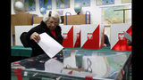 A voter casts her ballot at a polling station in Warsaw, Poland, Sunday, Oct. 13, 2019. Poles are voting Sunday in a parliamentary election, that the ruling party of Jaroslaw Kaczynski is favored to win easily, buoyed by the popularity of its social conservatism and generous social spending policies that have reduced poverty. (AP Photo/Darko Bandic)