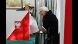 Voters inspect ballots at a polling station in Warsaw, Poland, Sunday, Oct. 13, 2019. Poles are voting Sunday in a parliamentary election, that the ruling party of Jaroslaw Kaczynski is favored to win easily, buoyed by the popularity of its social conservatism and generous social spending policies that have reduced poverty. (AP Photo/Darko Bandic)