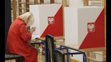 A woman votes by ballot in an election to the Polish parliament in Warsaw, Poland, on Oct. 13, 2019. Poles are voting Sunday in a parliamentary election, that the ruling party of Jaroslaw Kaczynski is favored to win easily, buoyed by the popularity of its social conservatism and generous social spending policies that have reduced poverty. (AP Photo/Czarek Sokolowski)